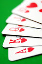 Royal flush of hearts poker cards closeup on green table Stock Photos