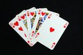 Royal flush poker hand in the heart suit against a black background Stock Photo
