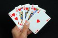 Royal flush poker hand in the heart suit against a black background Stock Photography