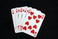 Royal flush poker hand in the heart suit against a black background Royalty Free Stock Photos