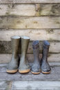 Rubber boots dirty on wooden floorboard Royalty Free Stock Images