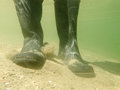 Rubber boots or gumboots underwater on sand ground closeup view of waders of a person walking in shallow water of gravel and beach Stock Photography
