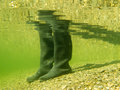 Rubber boots or gumboots underwater on sand ground closeup view of waders of a person walking in shallow water of gravel and beach Stock Images