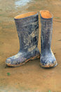Rubber boots muddy on wet ground Stock Image