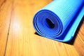 Rubber mat a blue rolled and ready to be used during the gymnastic exercises Stock Photo