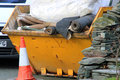 Rubbish skip close up of yellow full of trash and household waste Stock Image