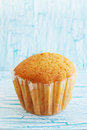 Ruddy muffin in the mold on wooden board Royalty Free Stock Image