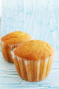 Ruddy muffins in the mold on wooden board Royalty Free Stock Photos