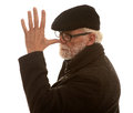 Rude senior man portrait of a in a flat cap making a gesture with his fingers and thumb on his nose white background Stock Photo