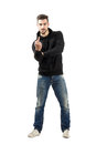 Rude young man in hoodie showing middle finger gesture full body length portrait isolated over white background Stock Photo