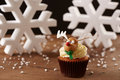 Rudolph reindeer cupcake on christmas background white snow flakes Stock Photography