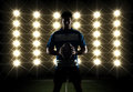 Rugby player silhouette in front of lights in a blue uniform Royalty Free Stock Image