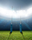 Rugby stadium and posts a with on a marked green grass pitch at night under illuminated floodlights Stock Photos