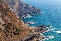 Rugged coastline view of a with steep barren cliffs falling down to a rocky shoreline with waves Stock Photo