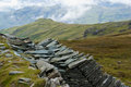Rugged landscape in the lake district with slate wall in foreground Royalty Free Stock Images