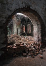 In the ruined church wall opening old light falls from collapsed roof Royalty Free Stock Photos