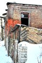 Ruined red brick house wall with window hole, snow covered fence wall Royalty Free Stock Photo