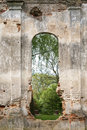 Ruined wall with vertical aperture and green park behind Royalty Free Stock Image