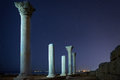 Ruins of ancient city columns under night sky blue with moon and stars Royalty Free Stock Photography
