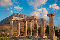 Ruins of appollo temple in corinth with fortress at back ancient greece Stock Photography