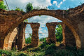 Ruins of church of Michael the Archangel in Yelets, overgrown arc of red brick and ruined columns Royalty Free Stock Photo
