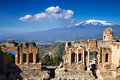 Ruins of the greek roman theater taormina sicily italy with etna erupting Royalty Free Stock Image