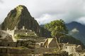 Ruins inside machu picchu peru with cloudy sky and sun peeking through and wayna in the background Stock Photography