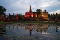 The ruins of Wat Mahathat in the festive lighting. Twilight in the historical Park of Sukhothai. Thailand