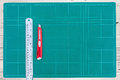 A ruler and cutter on green cutting mat Royalty Free Stock Photo