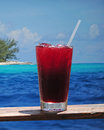 Rum punch or fruity drink in a tropical paradise with turquoise ocean and clear blue water Stock Photo