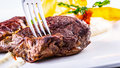 Rump steak. Close up Tender Grilled Beef Meat on White Plate with vegetable decoration. Royalty Free Stock Photo