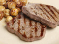 Rump steaks with mushrooms chargrilled sauteed button Royalty Free Stock Image