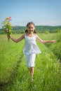 Run towards to summer little girl enjoys aroma of wild flowers Royalty Free Stock Photography