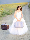 Runaway bride wearing a white wedding gown on the country road Stock Photo