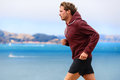 Runner athlete man running in sweatshirt hoodie autumn fall by the water male training outdoors jogging nature Stock Image