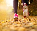 Runner close up of feet of a running in autumn leaves training exercise Royalty Free Stock Photography