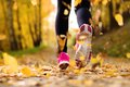 Runner close up of feet of a running in autumn leaves training exercise Stock Photos