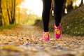 Runner close up of feet of a running in autumn leaves training exercise Stock Photo