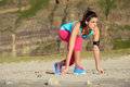 Runner with earphones ready for sprint fitness woman in running starting line position on the beach female fit before challenge Royalty Free Stock Images