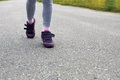 Runner feet running on road closeup on shoe girl fitness sunrise jog workout wellness concept Royalty Free Stock Photography