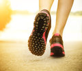 Runner feet running on road closeup on shoes woman fitness sunrise jog workout welness concept Royalty Free Stock Images