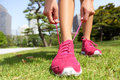 Runner getting ready tying running shoes laces for jogging woman preparing before run putting on trainers in japanese park near Stock Image
