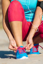 Runner lacing sport footwear female before running and fitness exercising on beach Royalty Free Stock Photo