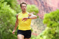 Runner looking at heart rate monitor smartwatch while running man jogging outside his sports smart watch during workout Royalty Free Stock Photography