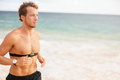 Runner man running with heart rate monitor on beach topless fit fitness athlete model jogging training for marathon run outside Royalty Free Stock Image