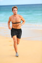 Runner man running with heart rate monitor on beach topless fit fitness athlete model jogging training for marathon run outside Stock Photos