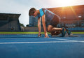 Runner ready for sports exercise young athlete at starting position to start a race male on racetrack with sun flare Royalty Free Stock Image