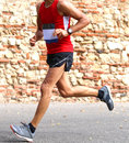 Runner runs fast race in town on a paved road