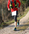Runner with sports wear during cross country on a country lane isolated road Stock Photos