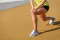 Runner stretching and knee pain fitness girl warming up before running in beach woman with running injury Stock Images